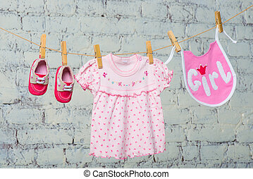 Children's bib, dress and red shoes for the girl, dry on a rope on a white brick wall.