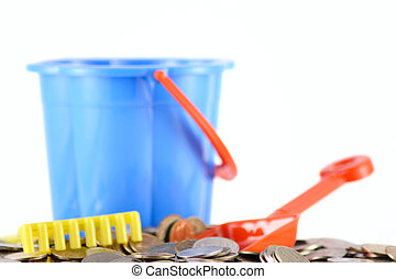 Childrens bucket with coins a scoop and a rake