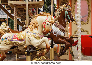 Children's carousel with horses in an amusement park. Empty carousel on a clear sunny autumn day.