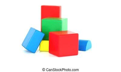 Childrens coloured bricks rotating on a white background