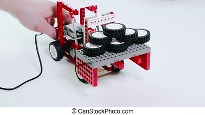 children's constructor loader raises toy wheels.