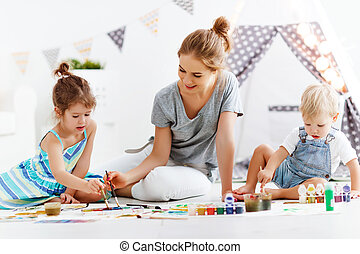 children's creativity. mother and children draw paints in ...