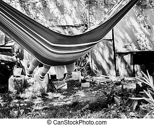 Children's feet in blue hammock on a background of the nature greenery. black and white photo