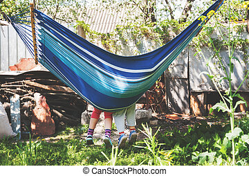 Children's feet in blue hammock on a background of the nature greenery. Vintage photo, vintage, retro, under the film