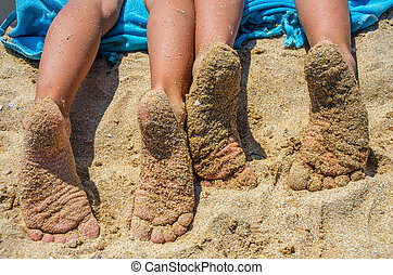 children's feet in sand