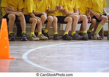 Children\'s feet in sports hall, sit on bench