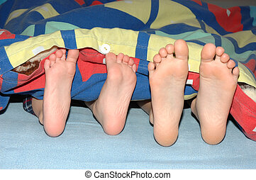 children's feet sticking out of cover
