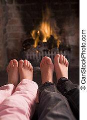 Children\\\'s feet warming at a fireplace