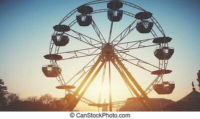 Children's Ferris wheel with cabs and umbrellas slowly...