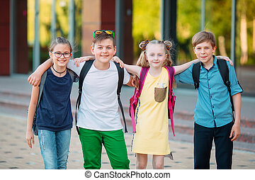 Children's friendship. Four little school students, two boys and two girls, stand in an embrace on the schoolyard