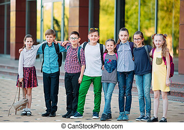 Children's friendship. Schoolmate students stand in an embrace on the schoolyard