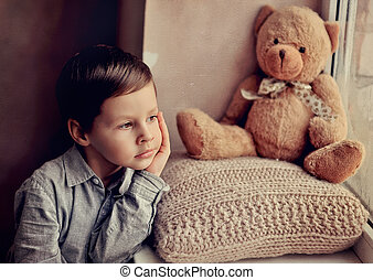children's grief - little boy with a toy on a knitted pillow...