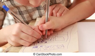 Childrens hands draw something in notebook, closeup view