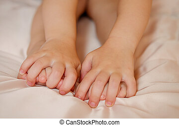 children's hands hold on to the legs of a small child, the baby sits on a crib in a bright room. warmth and tranquility, massage