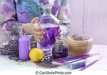 Children's hands holding a bottle of lavender oil
