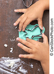 children's hands making christmas cookie