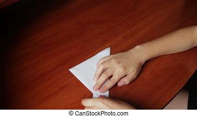children's hands making origami ship - children's hands do...