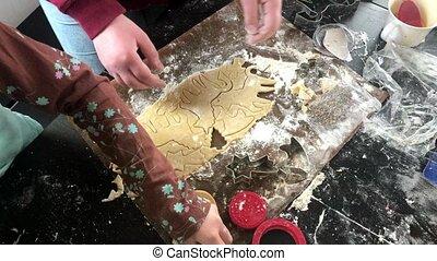 childrens' hands making unicorn shaped christmas cookies
