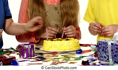 Children's hands turn put their candles in the cake, dressed bright things