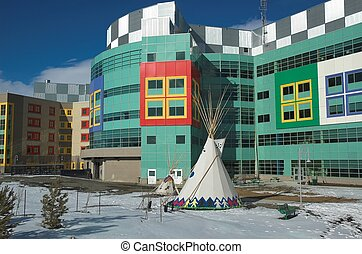 Modern hospital for the treatment of sick children in Calgary Alberta with blackfoot tepee in front.