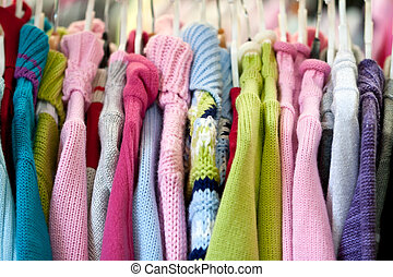 Children's knitted garments on hangers in shop