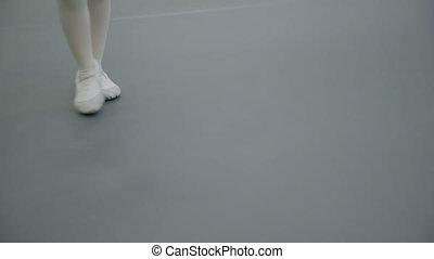 Children's legs in white training shoes dance on gray floor.