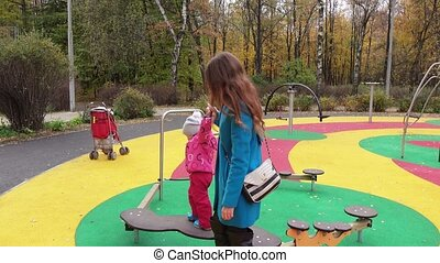 Children's obstacle course - Mom keeps the baby girl on the...