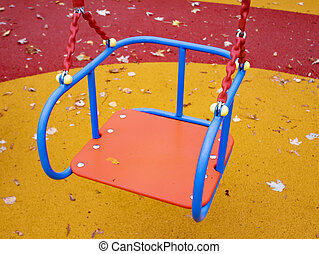 Children's playground with a swing in the autumn park.