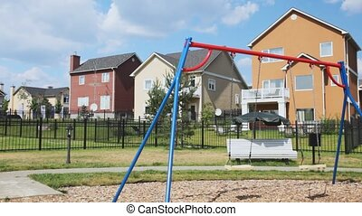 childrens playground with swing against country houses -...