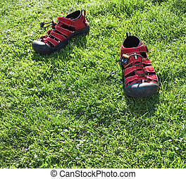 Children's red sandals on a green lawn