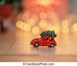 Children's red toy car carrying a Christmas tree