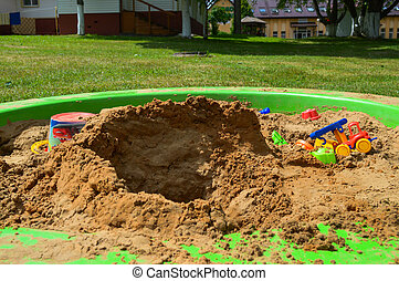 Children's sandbox on the playground for games with toys for children by truck, car, excavator, sand dressers with a spatula