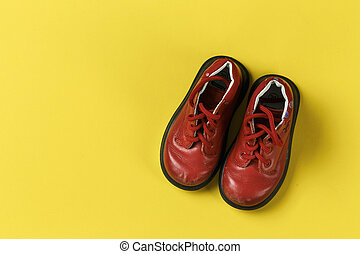 Children's shoes in red on a yellow background.