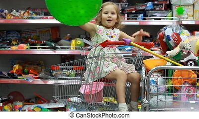 Children's shop with toys. A child in a supermarket sits in the shopping cart