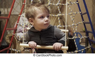 Children's swing in the room - Infant boy sits on a children...