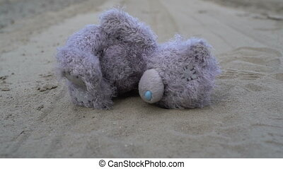 childrens toy gray plush teddy bear abandoned on dry cracked...