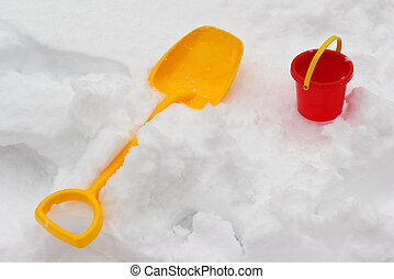 Children's toys - a yellow shovel and a red bucket on a snow