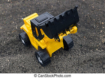 Children's toys excavator with a blade on the field
