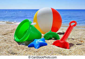 Children's toys on the beach against the blue sea and sky