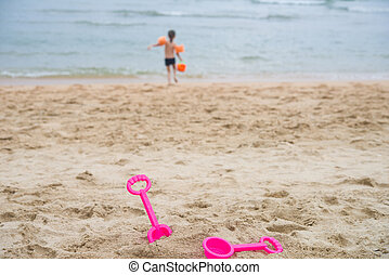 Children's toys on the beach, child in background carries ...