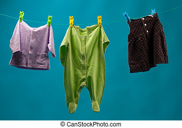 children\'s wear - Baby clothes on the line, on a blue...