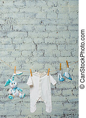 Children's white bodik, boots, panties and a toy rabbit dry on a rope against a white brick wall.