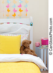 Child\'s bedroom with a teddy bear on the bed