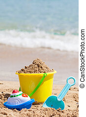 Child's bucket, spade and other toys on tropical beach against blue sky