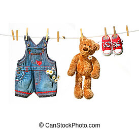Child's clothes with teddy bear on clothesline on white