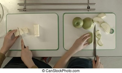 Child's cutting apple and cheese view from the top. Kids little girl and boy cooking at kitchen
