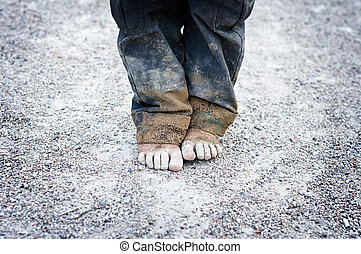 child's dirty feet - dirty and bare child's feet on gravel. ...