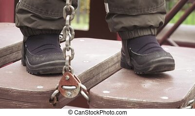 Child's feet on hanging wooden