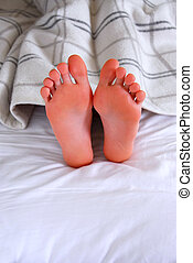 Child's feet sticking out of a blanket in a bed