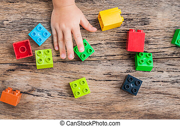 Child's hand and colorful toy building cubes. Top view.